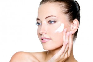 Beautiful woman applying moisturizer cosmetic cream on cheek - on a white