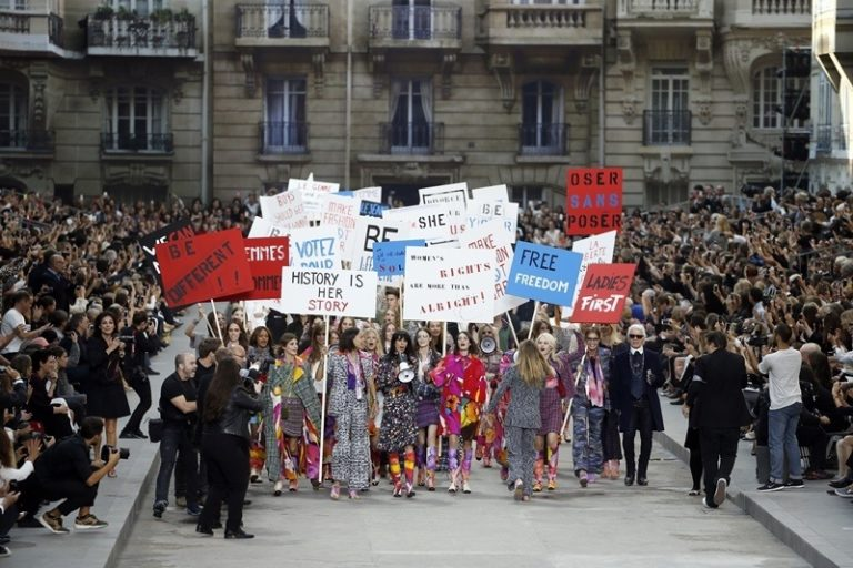 Models fake a demonstation as they present creations for Chanel next to German fashion designer Karl Lagerfeld (R) during the 2015 Spring/Summer ready-to-wear collection fashion show, on September 30, 2014 at the Grand Palais in Paris. AFP PHOTO / PATRICK KOVARIK        (Photo credit should read PATRICK KOVARIK/AFP/Getty Images)
